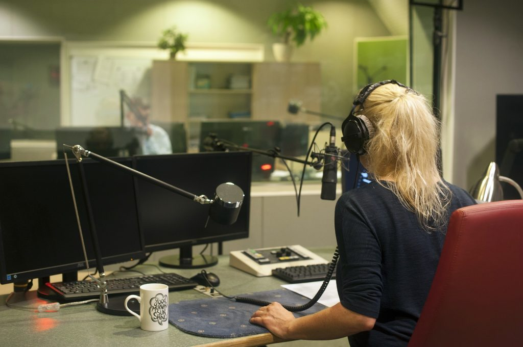 radio studio, female host with headphones and microphone, currently broadcasting