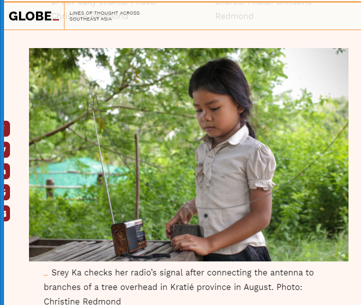 A little girl places the antenna wire on a tree to improve the reception quality of the lesson transmitted by radio.